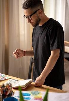 Portret van een geconcentreerde mannelijke kunstenaar die bij een tafel staat te tekenen in een schilderles in een studio