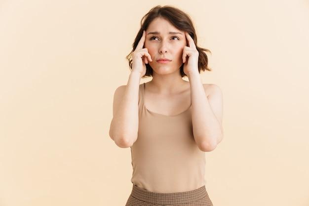 Portret van een geconcentreerde verbaasde vrouw van 20, gekleed in vrijetijdskleding die fronst en haar slapen aanraakt, geïsoleerd