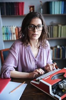 Portret van een geconcentreerde volwassen authoress zitten aan de tafel