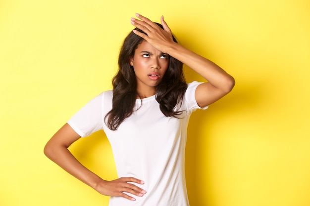 Portret van een geërgerd afro-amerikaans meisje, klap op het voorhoofd en rolt met haar ogen, vergat iets belangrijks, staande over gele achtergrond.