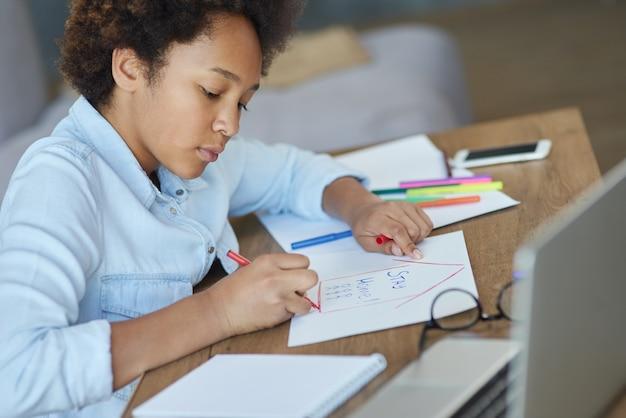 Portret van een gefocust tienerschoolmeisje dat markeringen gebruikt terwijl ze haar huiswerk doet met een laptopcomputer op