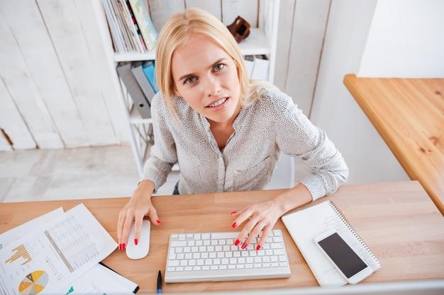 Portret van een gefrustreerde blonde vrouw die op de computer werkt en naar de voorkant kijkt