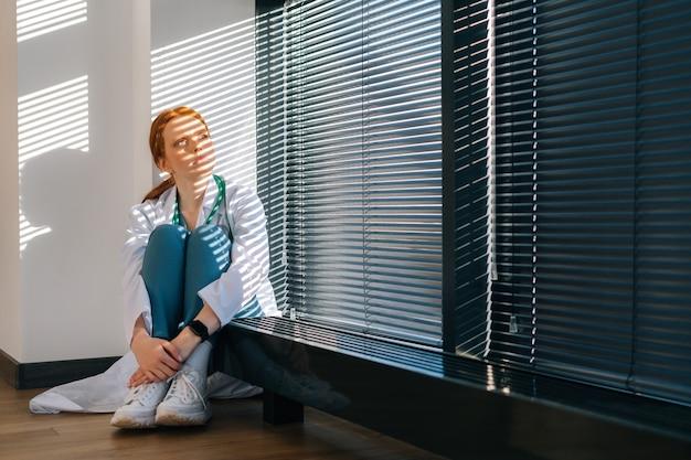 Portret van een gefrustreerde jonge vrouwelijke arts met een witte jas die op de vloer zit en de benen omhelst met de handen bij het raam in de lichte kantoorruimte van de medische kliniek.