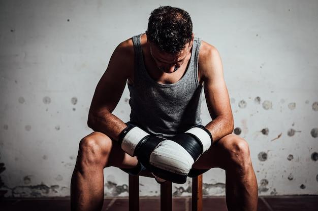 Portret van een gehandschoende bokser zittend op een bankje op zijn oefenterrein