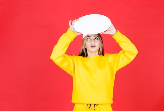 Portret van een geïnteresseerd meisje dat op zoek is naar een tekstballon in een witboekwolk