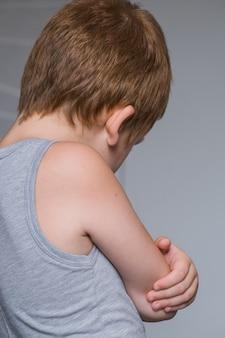 Portret van een geïrriteerd en ongelukkig kaukasisch kind met gekruiste armen terug verstoord en boos kindconcept