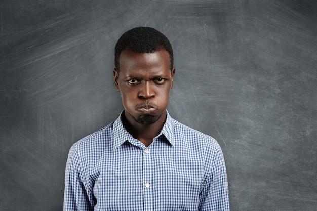 Portret van een geïrriteerde jonge donkere leraar die met een norse en boze uitdrukking kijkt, zijn wangen blaast, vol woede en ongeduld, boos op zijn studenten, probeert te kalmeren.