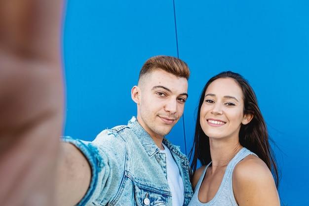 Portret van een geïsoleerd jong en gelukkig paar dat een selfie met een smartphone in blauw neemt