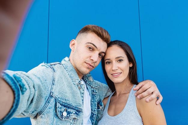 Portret van een geïsoleerd jong verliefd paar dat een selfie met een smartphone in blauw neemt