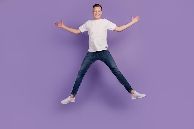 Portret van een gekke dromerige positieve kerel die springt, veel plezier op een paarse achtergrond