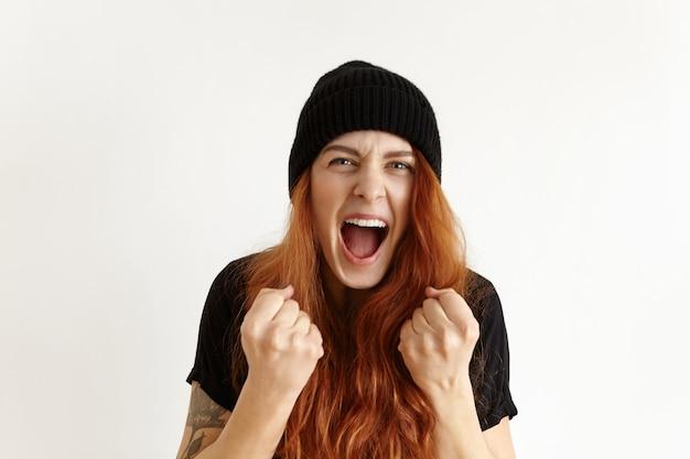 Portret van een gekke en woedende jonge roodharige vrouw die in hipsterhoed woede en woede uitdrukt