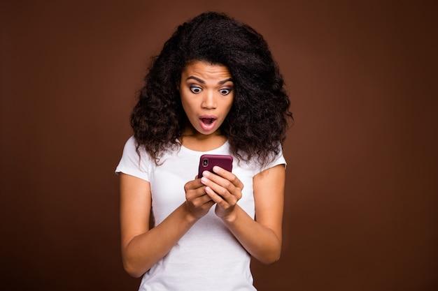 Portret van een gekke, funky afro-amerikaans meisje gebruik slimme telefoon lees sociale netwerkinformatie onder de indruk schreeuw wow omg draag casual stijlkleding.