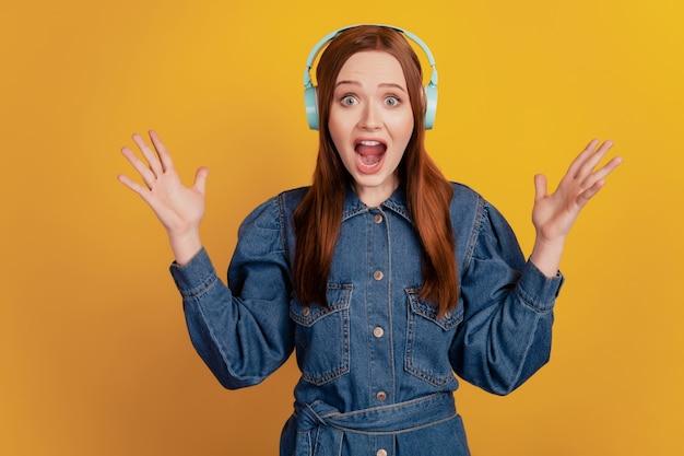 Portret van een gekke, funky dame, draag een koptelefoon, luister naar muziek, hef de handpalmen op en schreeuw open mond op gele achtergrond