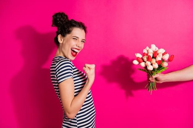 Portret van een gekke gelukkige meisjedatum met vriendje ontvangt bos tulpen, vuisten en schreeuwen