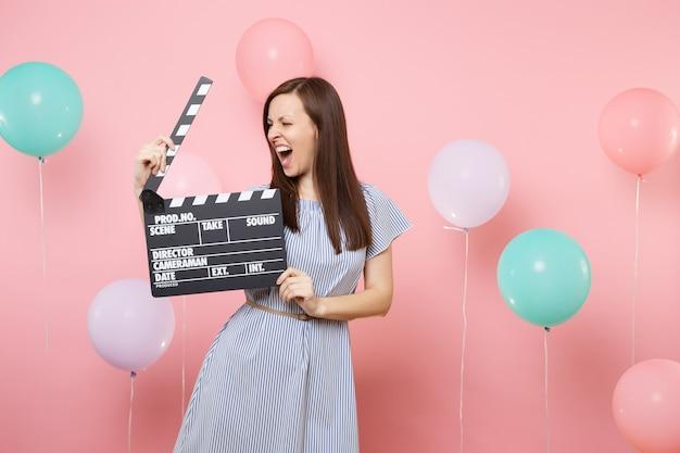 Portret van een gekke jonge vrouw die een blauwe jurk draagt die schreeuwt met klassieke zwarte film die filmklapper maakt op een roze achtergrond met kleurrijke luchtballonnen. verjaardag vakantie feest mensen oprechte emoties.
