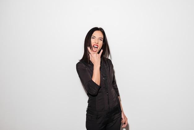 Portret van een gekke jonge vrouw die tong toont