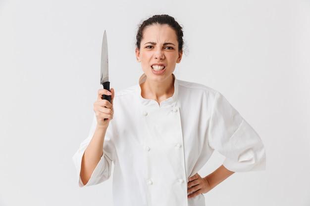 Portret van een gekke jonge vrouw met keukengerei