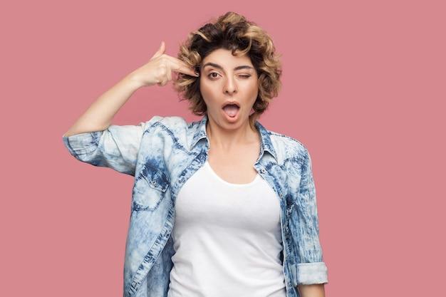 Portret van een gekke jonge vrouw met krullend kapsel in een casual blauw shirt dat met een pistoolhandpistool op haar hoofd staat en naar de camera kijkt. indoor studio opname, geïsoleerd op roze achtergrond.