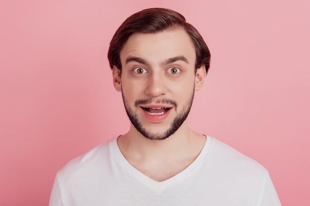 Portret van een gekke opgewonden verbaasde man met open mond op roze achtergrond
