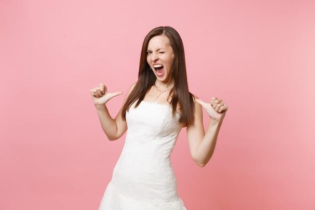 Portret van een gekke vrouw in een prachtige witte kanten jurk die schreeuwt met haar ogen en met haar duimen naar zichzelf wijst