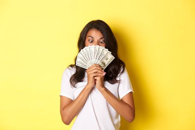 Portret van een gelukkig afro-amerikaans meisje dat een geldprijs wint die contant geld vasthoudt en er verbaasd uitziet staand