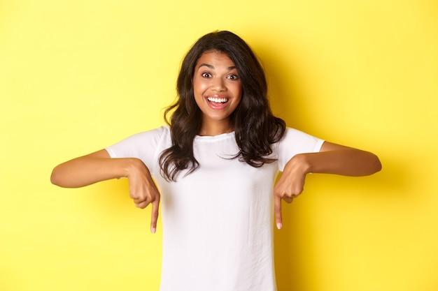 Portret van een gelukkig afro-amerikaans tienermeisje dat een spandoek toont, met de vingers naar de kopieerruimte wijst en opgewonden glimlacht, staande over een gele achtergrond.