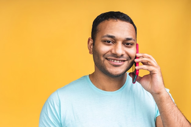 Portret van een gelukkig afro-amerikaanse zwarte indiase man praten op mobiele telefoon geïsoleerd op gele achtergrond.
