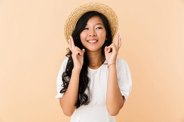Portret van een gelukkig aziatisch geïsoleerd meisje in de zomerhoed