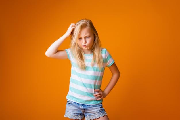 Portret van een gelukkig blond meisje in een blauw t-shirt op een gele muur