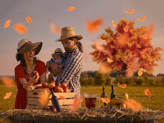 Portret van een gelukkig gezin bestaande uit moeder, vader en pasgeboren baby geportretteerd in een scène van het dagelijks leven op het platteland bij zonsondergang in de herfstperiode.