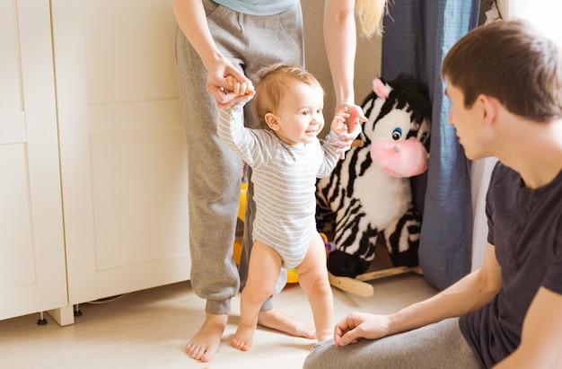 Portret van een gelukkig gezin dat lacht terwijl de baby zijn eerste stapjes zet