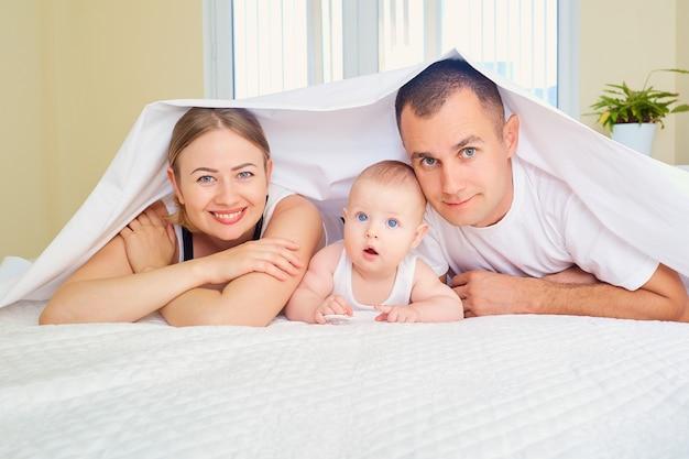 Portret van een gelukkig gezin in de kamer op het bed, moeder, vader en babyjongen, liggend op het bed, verborgen met een deken glimlachend