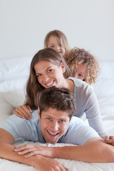 Portret van een gelukkig gezin liggend op elkaar