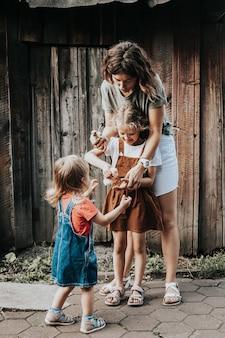 Portret van een gelukkig gezin van moeder met dochters die een kleine kip in hun handen houden