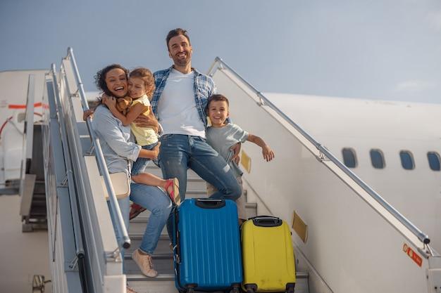 Portret van een gelukkig gezin van vier dat overdag uit het vliegtuig stapt. mensen, reizen, vakantieconcept
