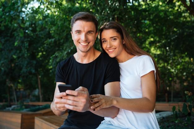 Portret van een gelukkig glimlachend paar dat mobiele telefoon houdt