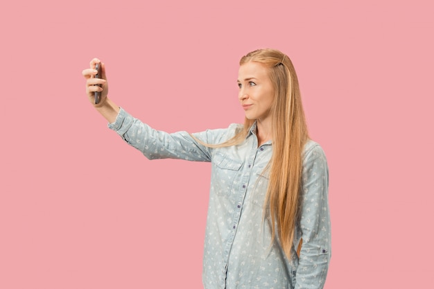 Portret van een gelukkig glimlachend toevallig meisje die de lege het scherm mobiele telefoon tonen die over roze muur wordt geïsoleerd