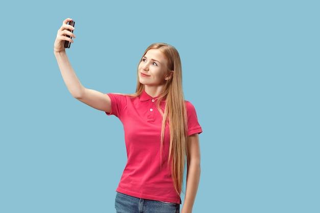 Portret van een gelukkig glimlachend toevallig meisje die de lege mobiele telefoon van het scherm tonen die over blauwe achtergrond wordt geïsoleerd