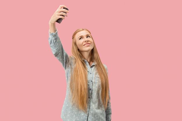 Portret van een gelukkig glimlachend toevallig meisje die de lege mobiele telefoon van het scherm tonen die over roze achtergrond wordt geïsoleerd