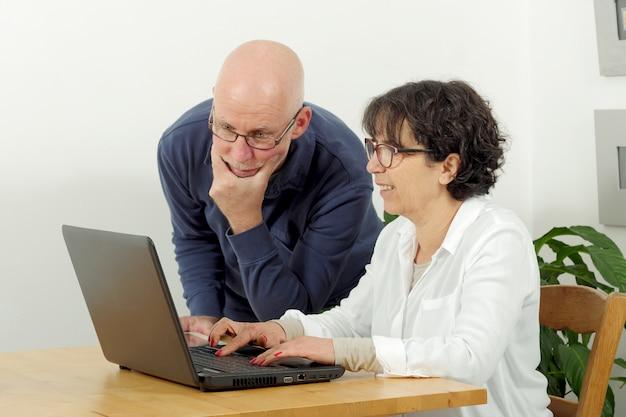 Portret van een gelukkig hoger paar dat laptop met behulp van