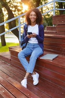 Portret van een gelukkig jong afrikaans meisje met rugzak met behulp van mobiele telefoon tijdens het rusten in het park