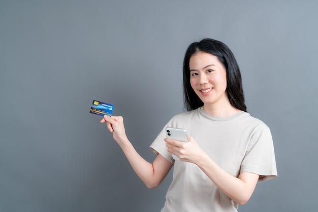 Portret van een gelukkig jong aziatisch meisje dat plastic creditcard toont terwijl het houden van mobiele telefoon op grijze muur