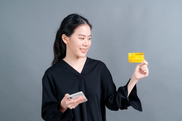 Portret van een gelukkig jong aziatisch meisje dat plastic creditcard toont terwijl hij mobiele telefoon vasthoudt
