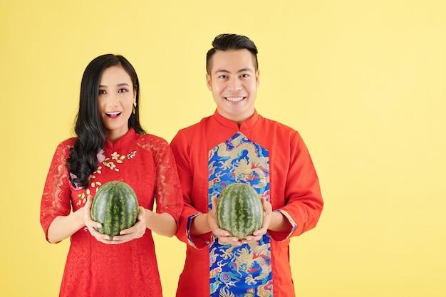 Portret van een gelukkig jong aziatisch stel in traditionele kostuums voor het nieuwe maanjaar met verse rijpe watermeloenen