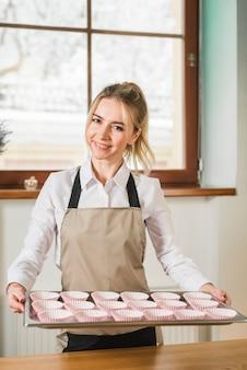 Portret van een gelukkig jong die dienblad van de vrouwenholding met lege cupcake gevallen wordt gevuld