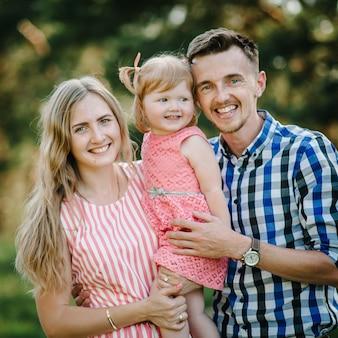 Portret van een gelukkig jong gezin dat samen tijd doorbrengt in de natuur op zomervakantie. de vader, moeder en meisje lopen en spelen in het park bij zonsondergang. detailopname.