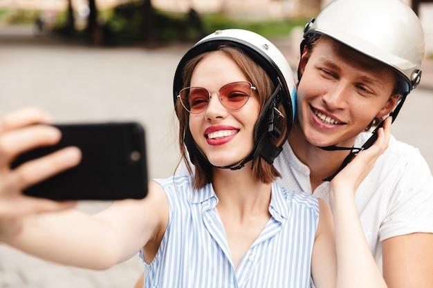 Portret van een gelukkig jong koppel in helmen rijden op een motor samen in de stad straat, een selfie nemen
