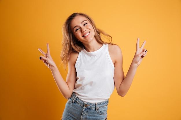 Portret van een gelukkig jong meisje dat vredesgebaar toont