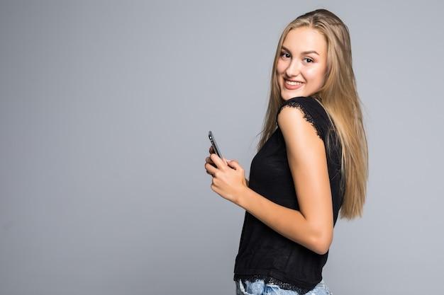 Portret van een gelukkig jong meisje met behulp van smartphone geïsoleerd op een grijze achtergrond