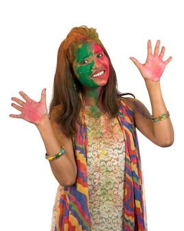 Portret van een gelukkig jong meisje met een kleurrijk gezicht op holi-kleurenfestival op wit